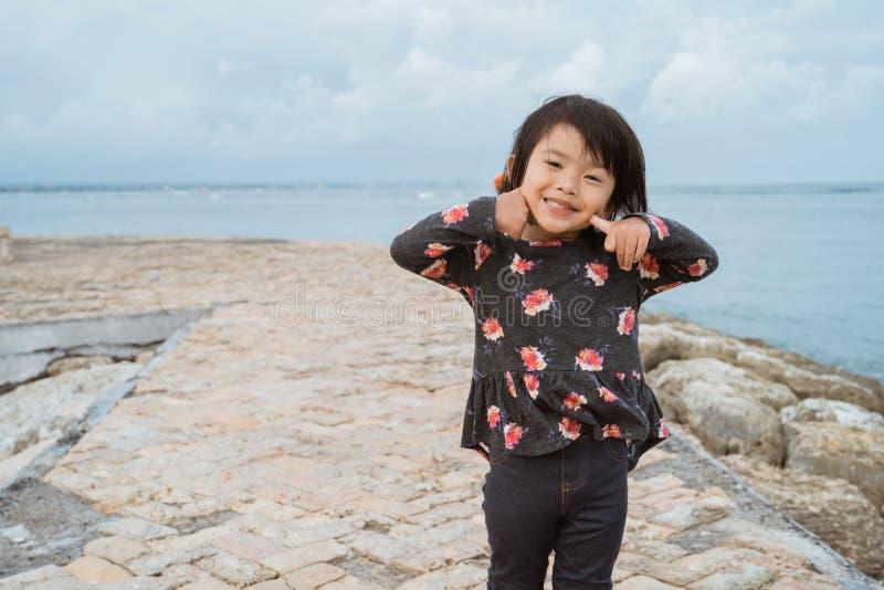 与逗人喜爱的面孔微笑的亚洲女孩姿势,当看看在海滩的照相机 库存图片