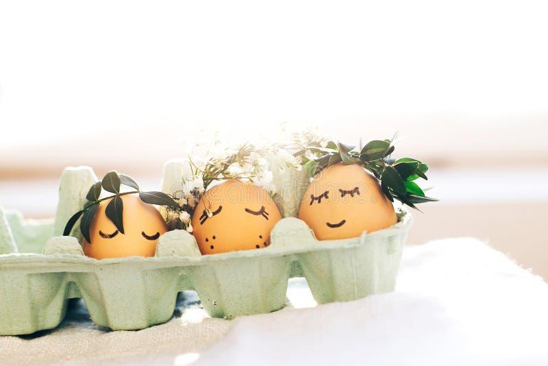 与逗人喜爱的面孔的时髦的复活节彩蛋在纸盒盘子的花卉花圈冠在土气背景 与花的现代复活节彩蛋 免版税库存照片