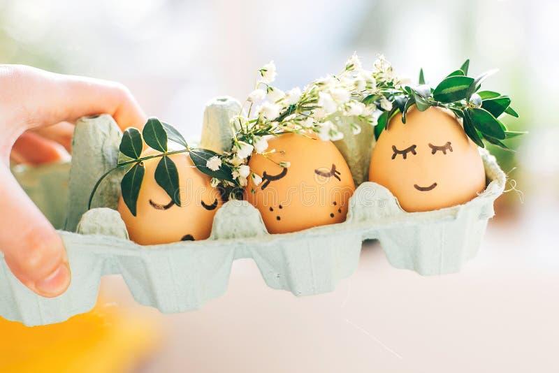 与逗人喜爱的面孔的时髦的复活节彩蛋在纸盒盘子的花卉花圈冠 与花和困眼睛的现代甜复活节彩蛋 免版税库存图片