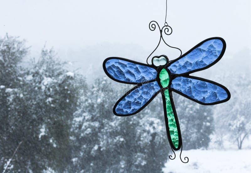 与通过与垂悬在windo的明亮的蓝色和绿色冰屑玻璃蜻蜓太阳俘获器的一个窗口被看见的橡树的冷的雪天 免版税库存照片