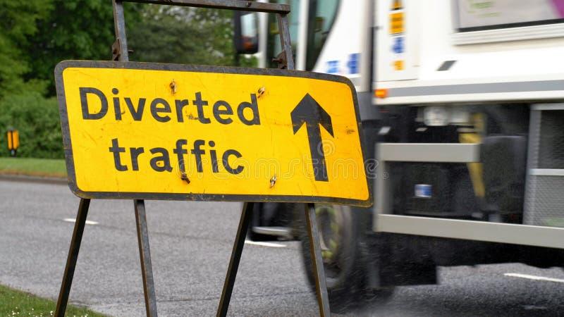 与通过在英国路的背景的汽车和卡车的被牵制的交通标志 免版税库存图片
