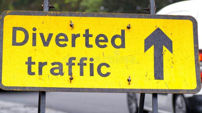 与通过在英国路的背景的汽车和卡车的被牵制的交通标志 库存图片
