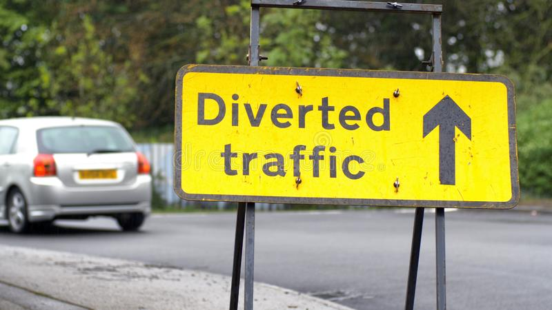 与通过在英国路的背景的汽车和卡车的被牵制的交通标志 免版税库存照片