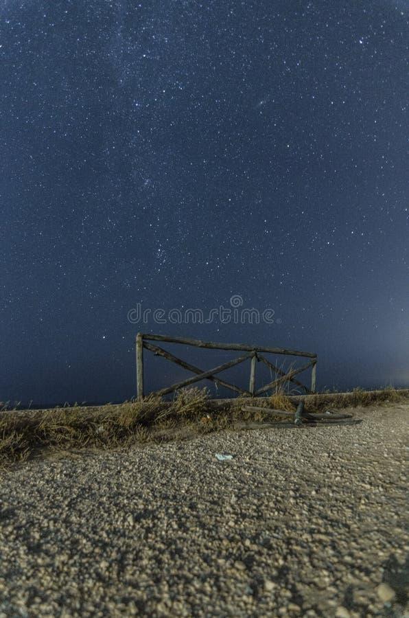 与道路和满天星斗的天空的夜风景 免版税库存照片