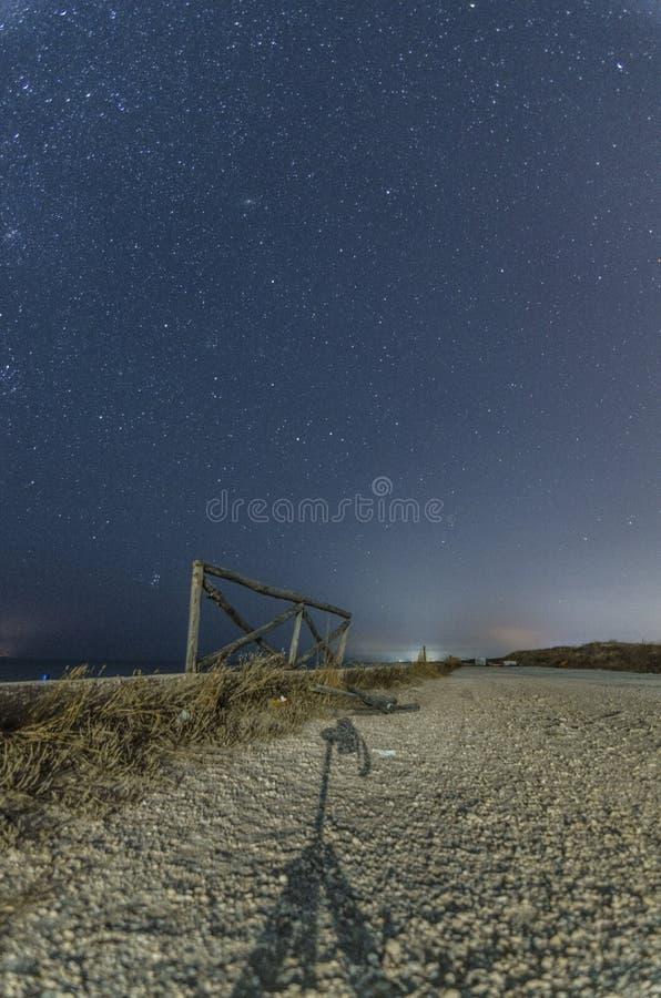 与道路和满天星斗的天空的夜风景 免版税图库摄影