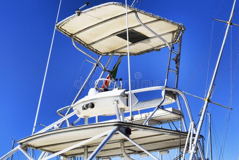 与遮篷和一条使用的白色小船的船舶辅助部件的Flybridge 免版税库存照片