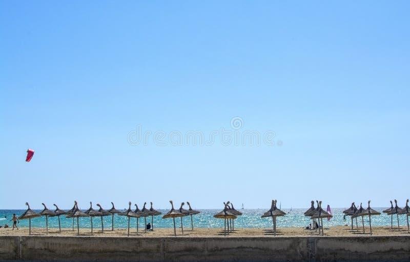 与遮阳伞、浩大的天空蔚蓝和kitesurfers的沙滩 免版税图库摄影
