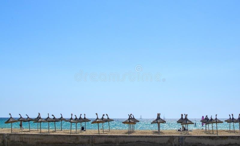 与遮阳伞、浩大的天空蔚蓝和kitesurfers的沙滩 免版税库存照片