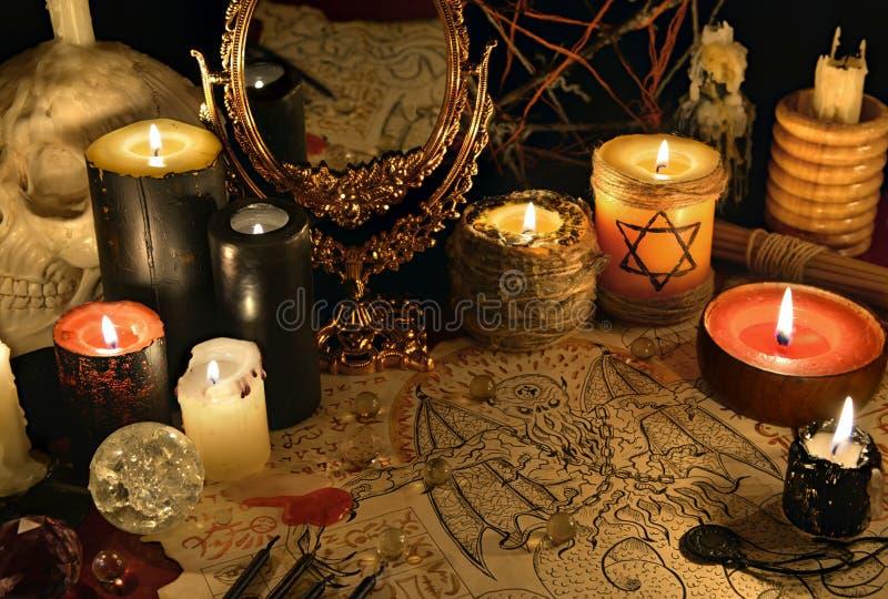 与邪魔原稿、镜子和黑蜡烛的神秘的静物画 图库摄影