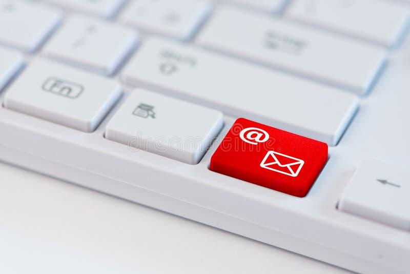与邮件象标志的一把红色钥匙在白色膝上型计算机键盘 图库摄影