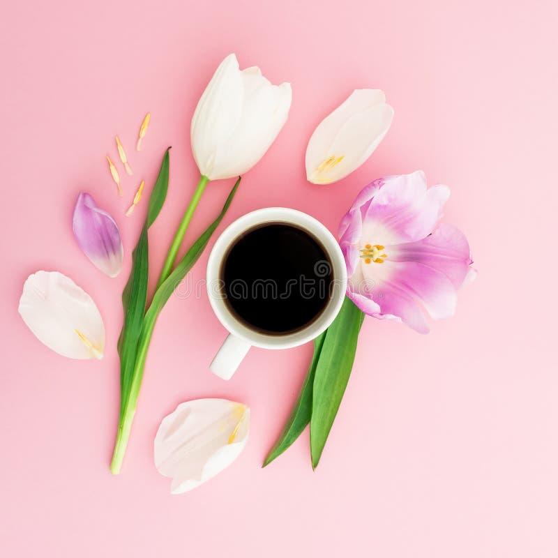 与郁金香、瓣和杯子的夏天构成在桃红色背景的咖啡 平的位置,顶视图 库存图片