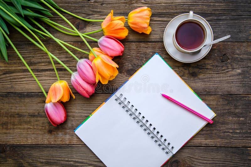 与郁金香的浪漫图片,茶,在木背景的笔记本 库存照片