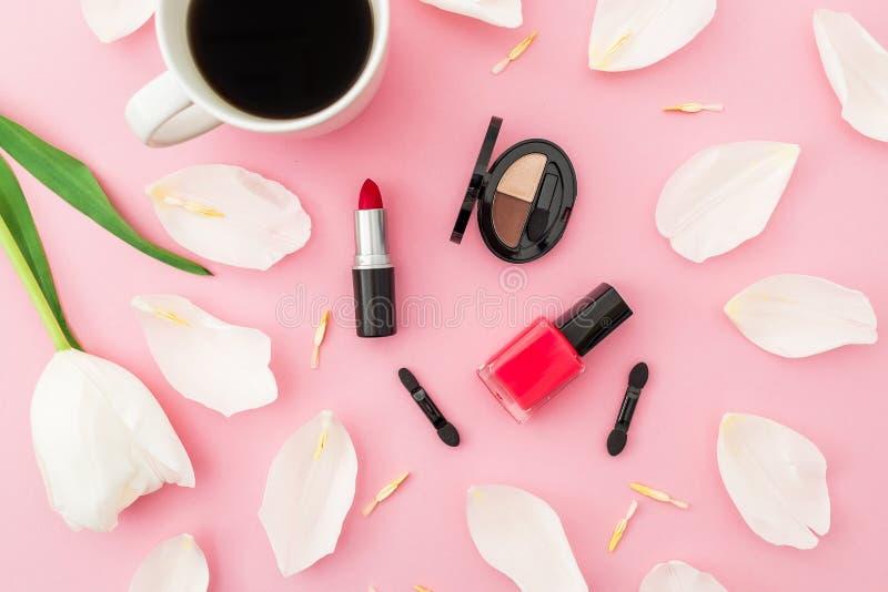 与郁金香花、咖啡杯和化妆用品的构成在桃红色背景 顶视图 免版税库存图片