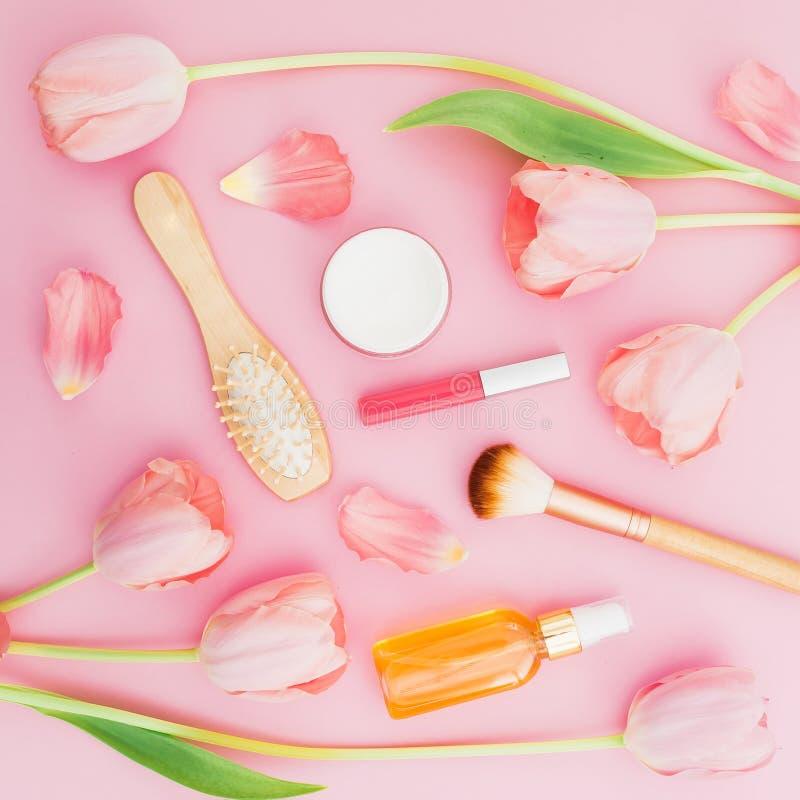 与郁金香花和构成女性化妆用品的秀丽构成,芳香和梳子在桃红色背景 顶视图 平的位置 免版税库存图片