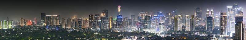 与都市摩天大楼的全景雅加达地平线在晚上 库存照片