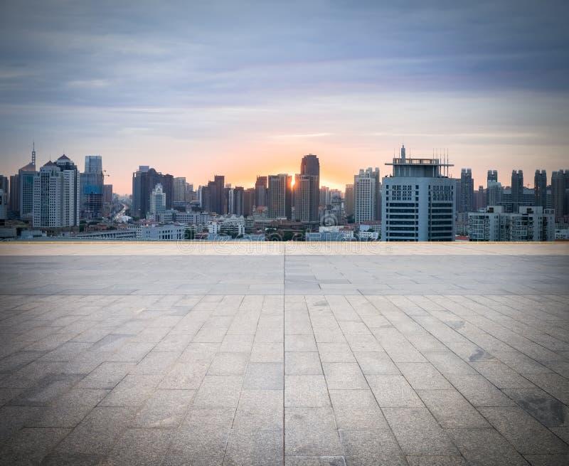 与都市风景和地平线的空的砖地板 图库摄影
