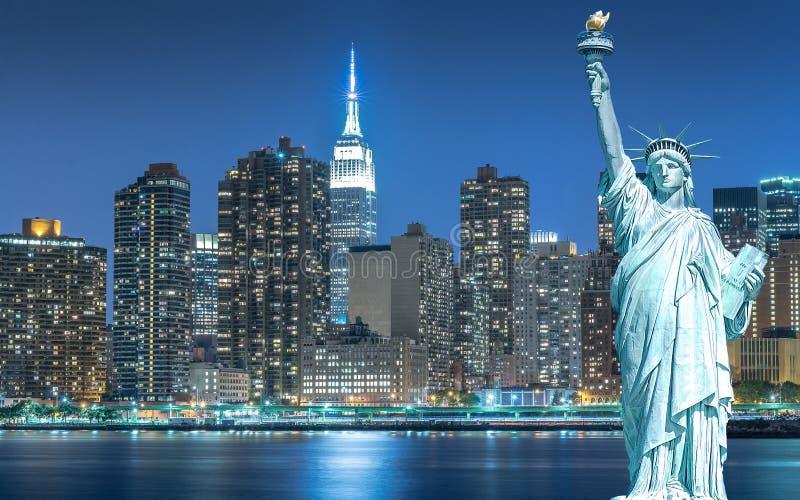 与都市风景的自由女神像在曼哈顿在晚上,纽约 库存图片