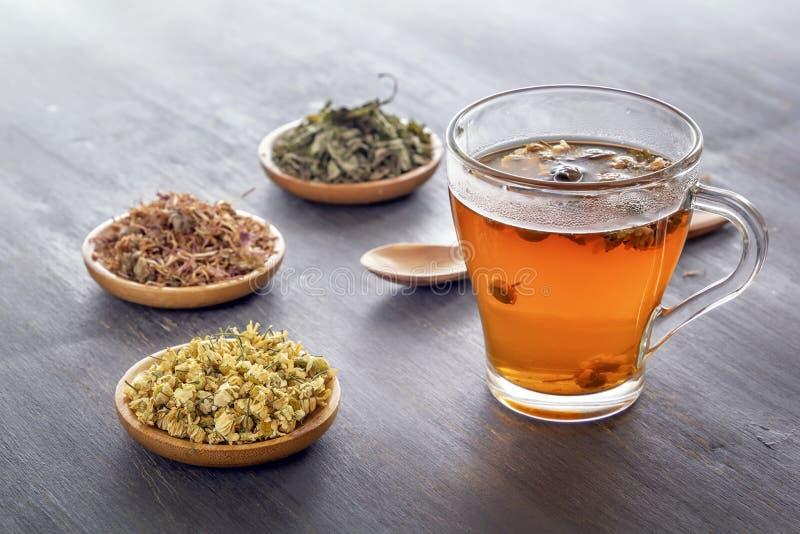 与配药春黄菊、干燥菊花和猎人的清凉茶在木桌上 图库摄影