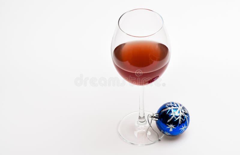 与酒和圣诞节装饰的玻璃 与酒精饮料的冬天庆祝 有红色液体或酒的葡萄酒杯和 免版税库存图片