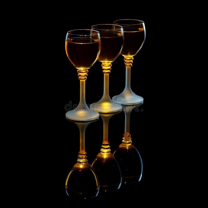 与酒精的三个小玻璃在黑背景 免版税库存图片