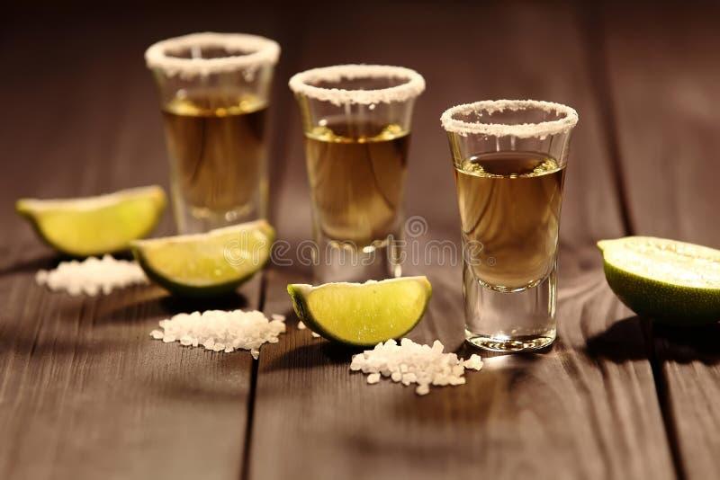 与酒精的三块短的玻璃在切片石灰和盐旁边在与葡萄酒纹理的一张老土气桌上 免版税库存图片