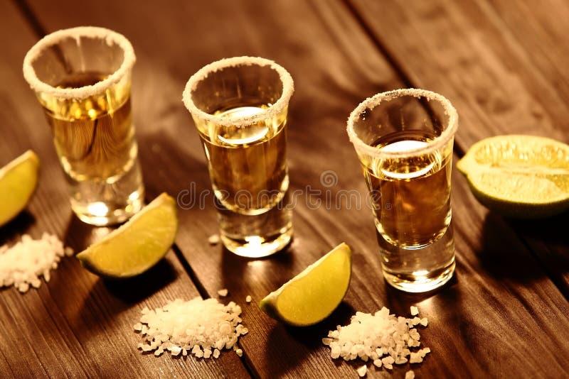 与酒精的三块短的玻璃在切片石灰和盐旁边在与葡萄酒纹理的一张老土气桌上 免版税图库摄影