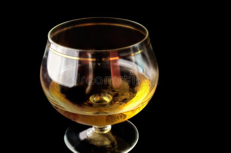 与酒精的小玻璃在黑背景 免版税库存照片