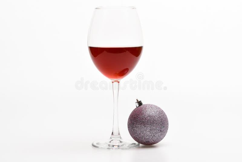 与酒精饮料的冬天庆祝 寒假概念 有红色液体或酒和圣诞节球的葡萄酒杯 库存图片