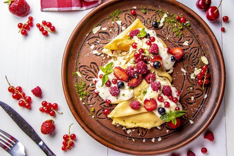 与酸性稀奶油和莓果在一个白色背景特写镜头,水平的照片的自创薄煎饼 库存照片