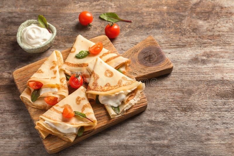 与酸性稀奶油和西红柿的稀薄的薄煎饼 库存图片