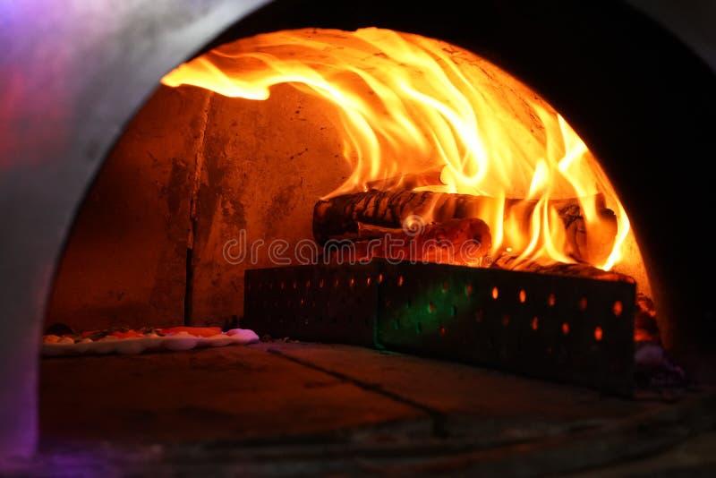 与里面火的葡萄酒老烤箱为烘烤原始的比萨 免版税库存照片