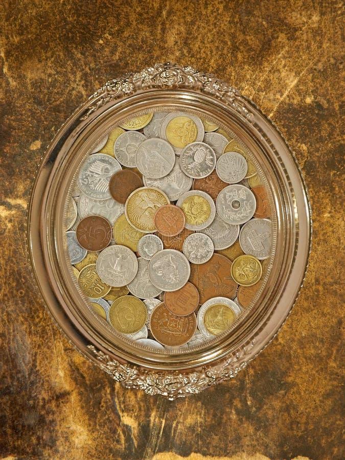 与里面货币硬币收集的金黄卵形照片框架。 库存照片