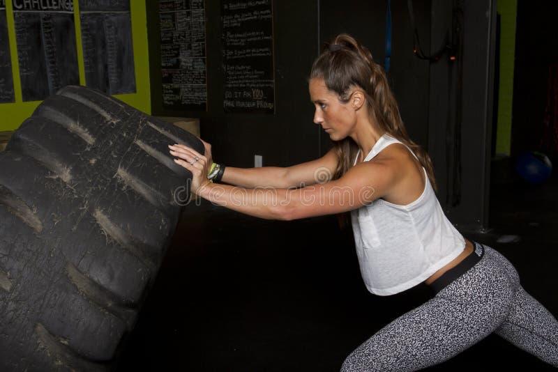 与重的拖拉机轮胎的女性健身教练员 库存照片