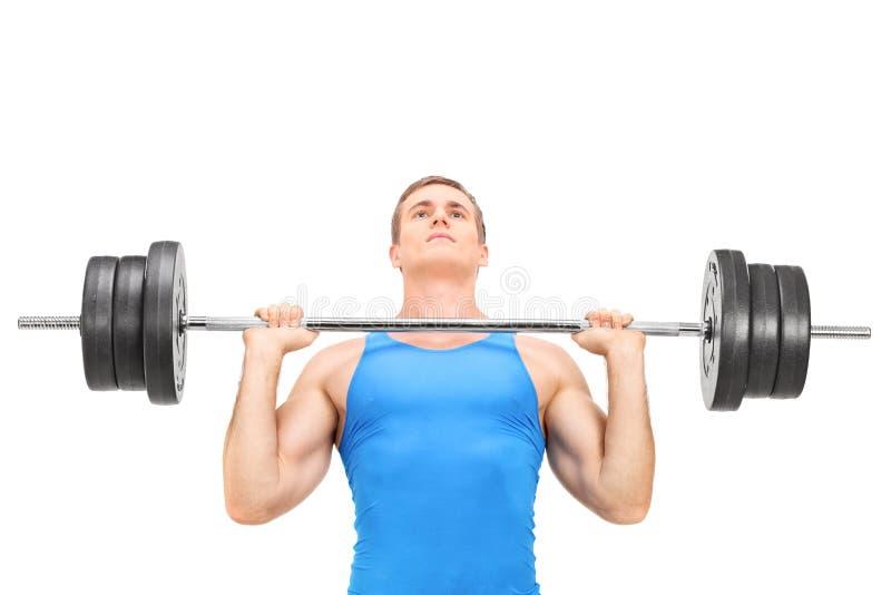 与重的杠铃的年轻举重运动员训练 库存图片