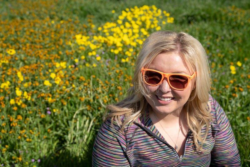 与野花和绿草的愉快的白肤金发的妇女姿势在春天 过敏的概念 免版税库存照片