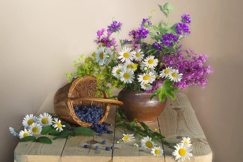与野花和莓果的花束在一张木桌上的一个篮子 库存照片