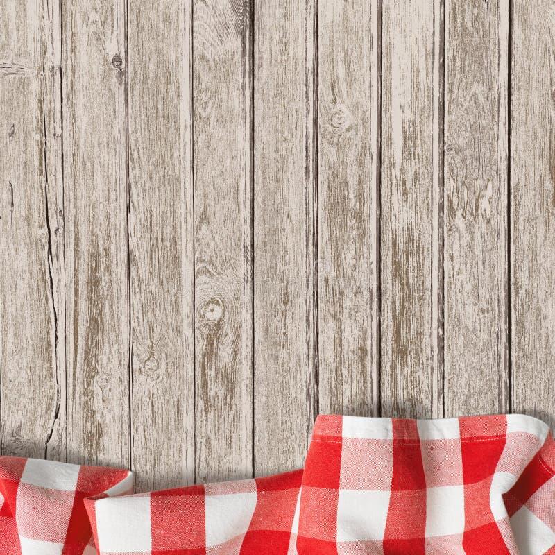 与野餐桌布的老木桌背景 免版税库存照片