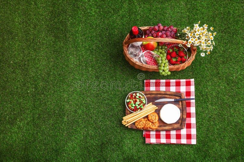 与野餐篮子、酒和产品的平的被放置的构成在草 免版税库存照片