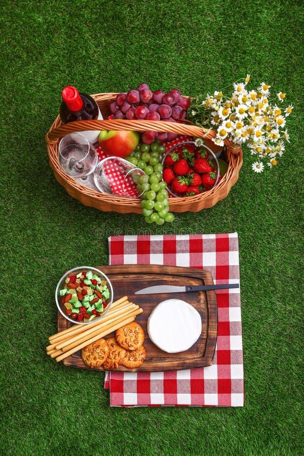 与野餐篮子、酒和产品的平的被放置的构成 免版税库存照片