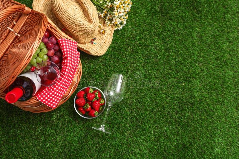 与野餐篮子、酒和果子的平的被放置的构成在草 库存照片