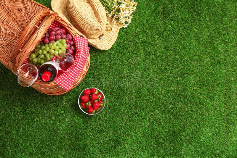 与野餐篮子、酒和果子的平的被放置的构成在草 库存图片