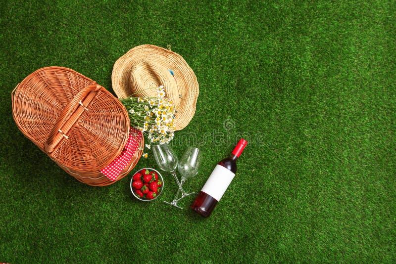 与野餐篮子、酒和草莓的平的被放置的构成在草 免版税库存照片