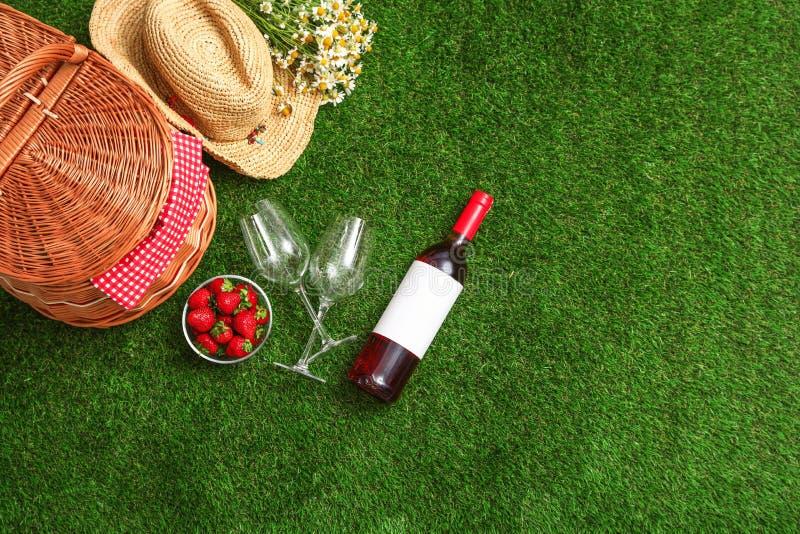 与野餐篮子、酒和草莓的平的被放置的构成在草 库存照片
