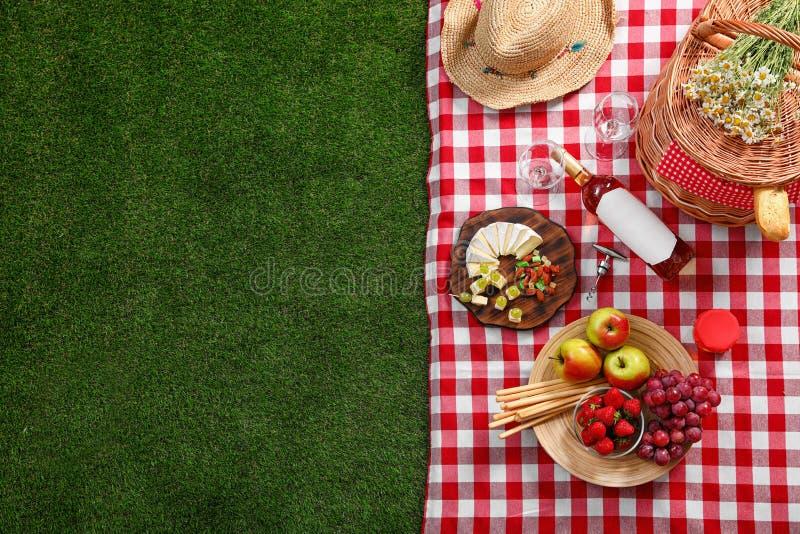 与野餐篮子的平的被放置的在室外方格的毯子的构成和产品 库存照片