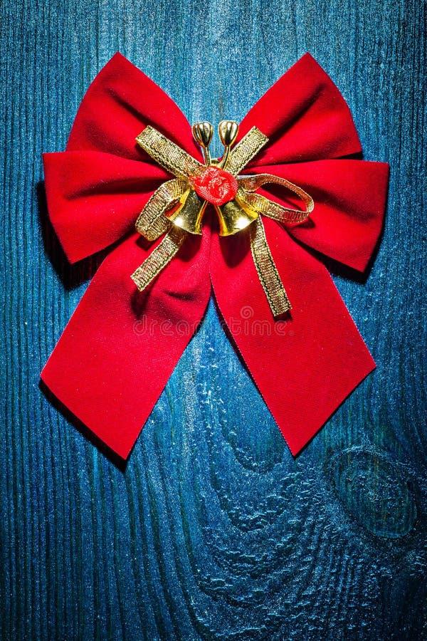 与金丝带和小的响铃的美好的红色圣诞节弓 免版税图库摄影