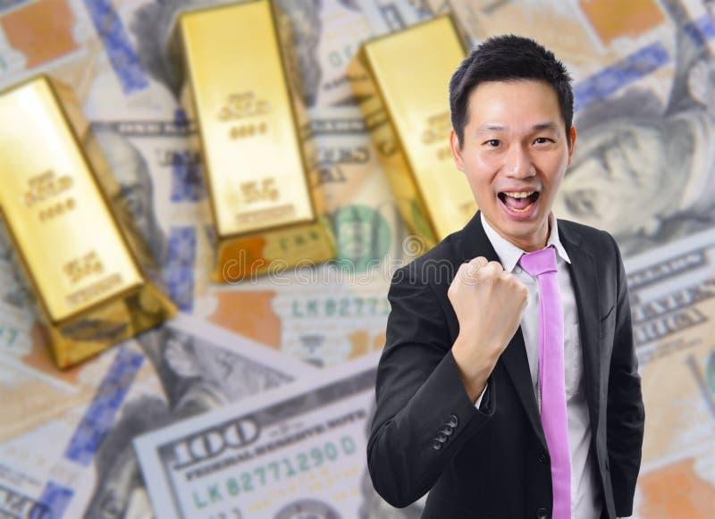 与金制马上的齿龈和美元钞票背景的愉快的商人 免版税库存图片
