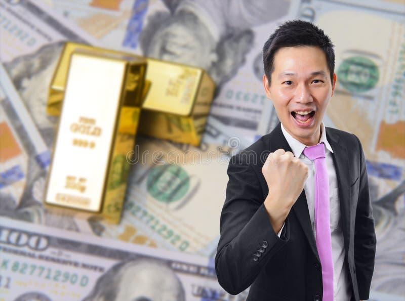 与金制马上的齿龈和美元钞票背景的成功亚洲商人 免版税库存照片