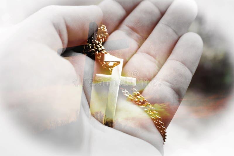 与金十字架的美好的耶稣基督艺术在手中与十字架在日落背景中 库存图片