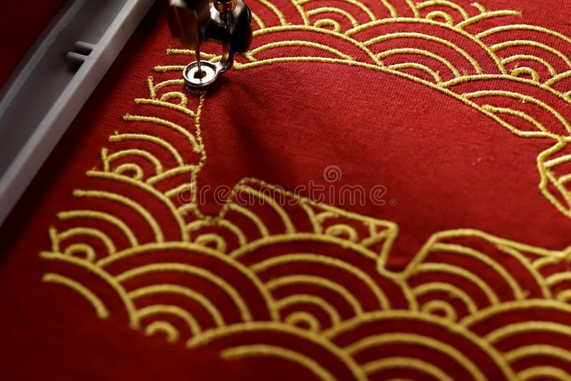 与金子的传统壳样式构筑的猪刺绣在欢乐轻的心情-春节概念的红色织品 免版税库存图片