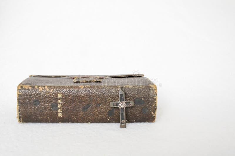 与金属和木头古色古香的十字架的古色古香的被佩带的皮革圣经  免版税库存图片
